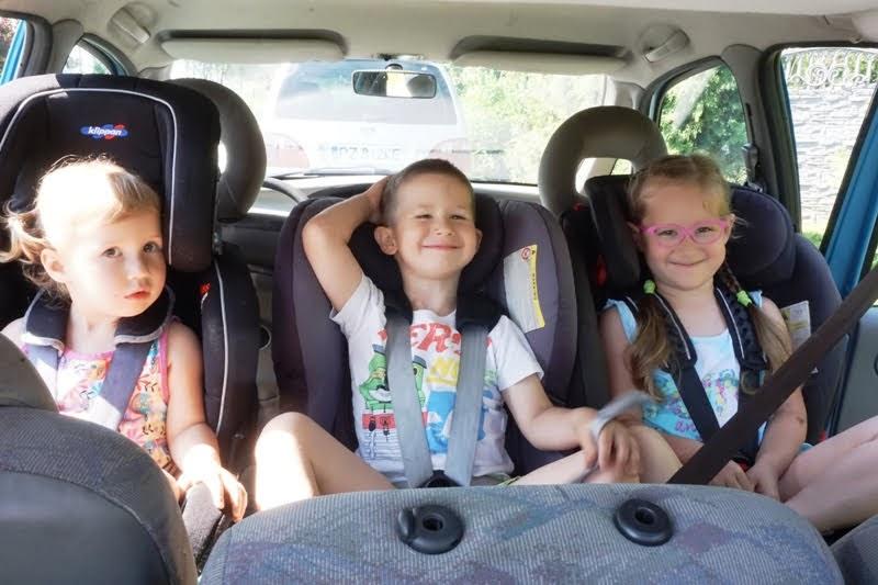 trójka dzieci na tylnim rzędzie auta w fotelikach RWF