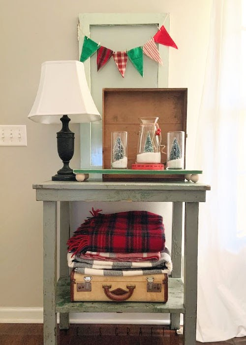 Christmas Vignette with DIY snow globes and bottle brush trees, plaid bunting, plaid blankets