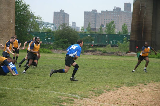Berto wearing a blue jersey with a white number 14 on the back running during a rugby match being pursued by opponents in yellow jerseys