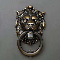 Ağzında demir bir halka olan aslan başlı kapı tokmağı