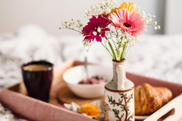 petit déjeuner au lit, plateau croissant, café et fleurs