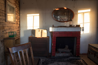 Interior architectural shot showing window light on a wall with a fireplace and chair in rural Texas, USA