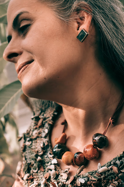 Mulher usando colar de cerâmica ao lado de uma árvore