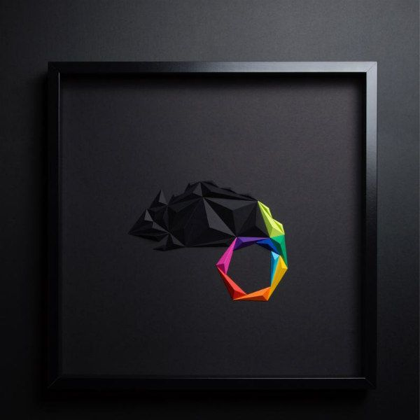3D black folded paper chameleon with brightly colored tail in square black frame on wall