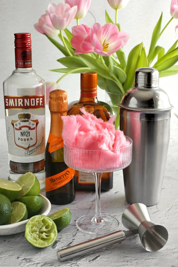Recipe for a Cosmopolitan cocktail version with vodka, cranberry juice, triple sec, lime juice, prosecco and cotton candy.