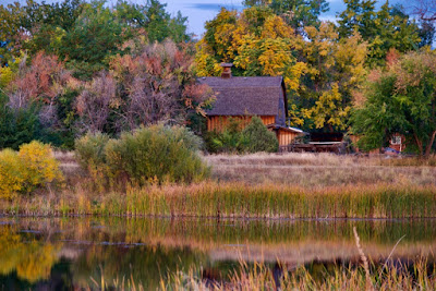 An old barn nestled among trees with changing colored leaves and reflected in the pond