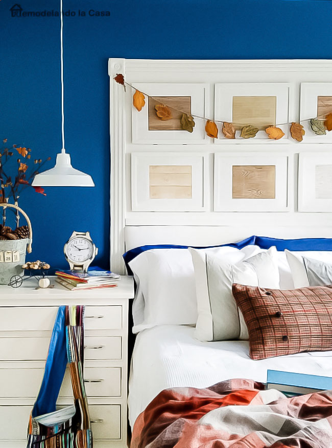 navy blue walls, picture frame headboard, plaid throw blanket, fall decor