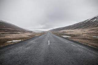 A view down a road in a somewhat bleak landscape, with low hills on either side. The sky is overcast above.