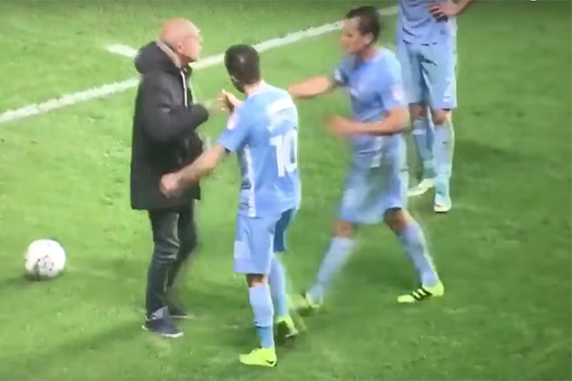 A Coventry fan walks onto the pitch and confronts the players