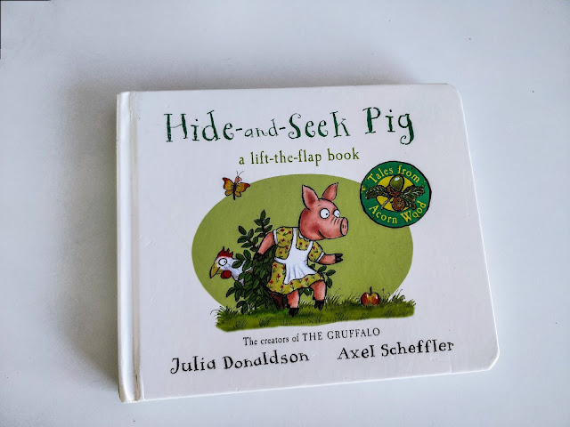 "A book sits on a white surface. The cover says ""Hide and Seek Pig"" in large green lettering. Below it says ""a lift-the-flap book"" in the same green. An illustration of a pig wearing yellow dress with flowers all over under a white apron while sneaking past a green bush to the left of the pig. A white hen is peeking out from the left of the bush. The ground beneath them is grassy with a green oval as a background behind the image. The bottom has text that reads ""The Creators of THE GRUFFALO"" Underneath reads Julia Donaldson to the left with Axel Scheffler to the right."