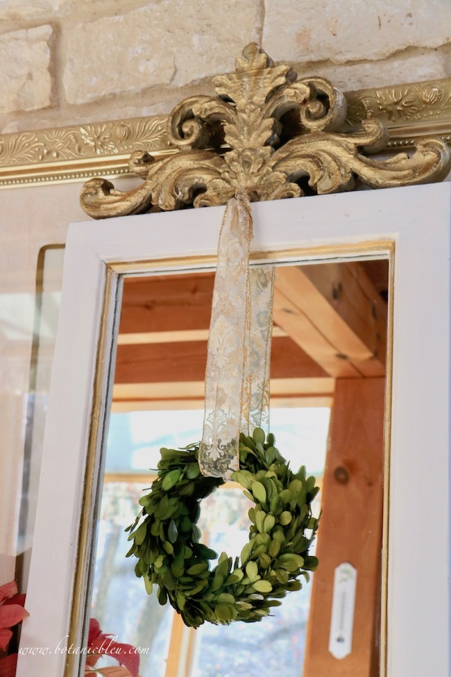 French country mirror decorated for Christmas with a boxwood wreath hanging from a gold and white fleur de lis ribbon