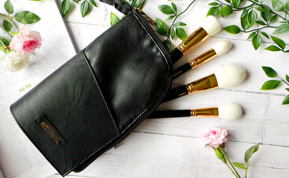 4 makeup brushes are sticking out of a black vegan leather pouch