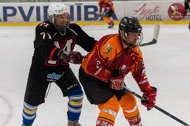 Hokejists melnā formā grūž mugurā pretinieku ar nūju