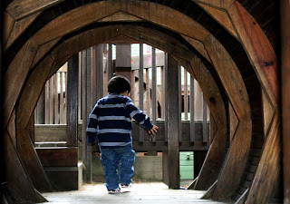 Boy walking away from the view through a play gym tunnel, exiting the tunnel into a larger play area