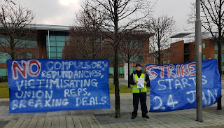 "Ian holding leaflets outside buildings, with banners reading ""No compulsory redundancies, victimisation of union reps, breaking deals"" and ""strike starts 24 Jan"""