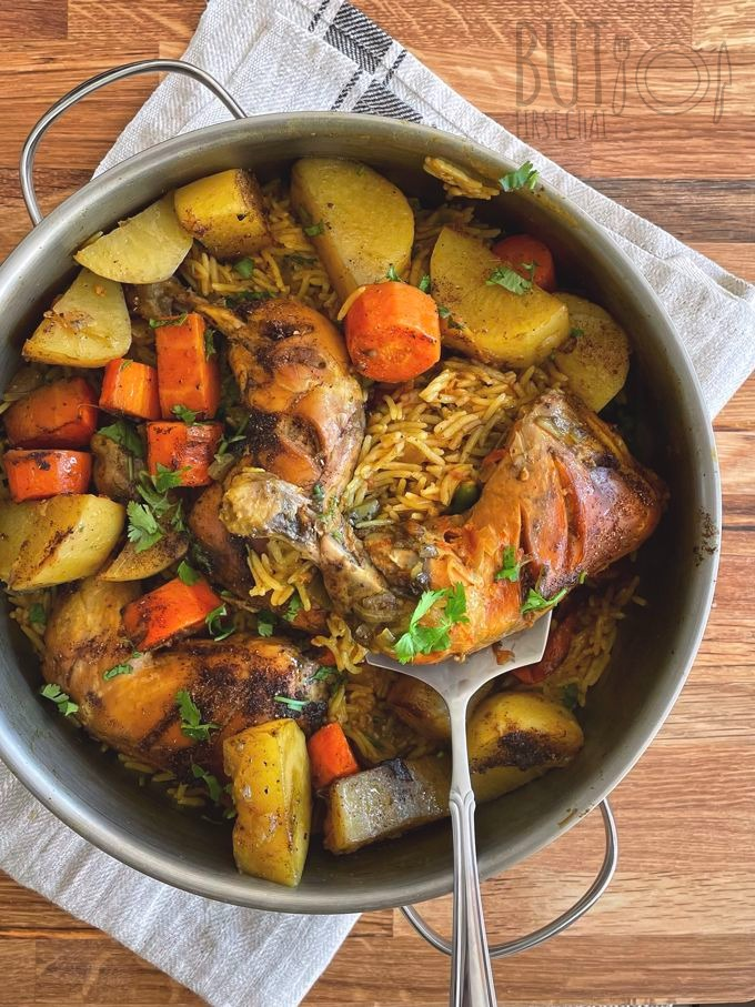 A pot of Chicken Machboos with carrots and potatoes