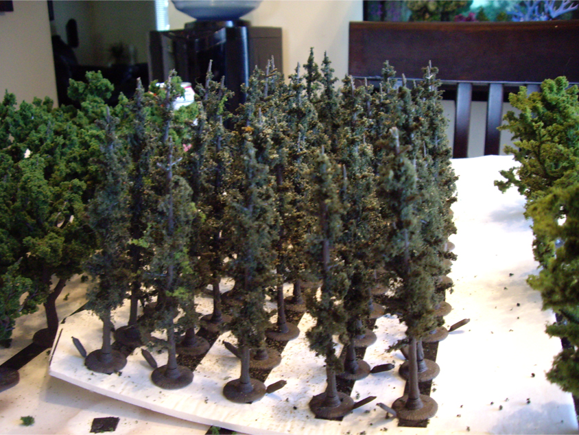 Several Woodland Scenics pine tree armatures covered with forest green ground foam