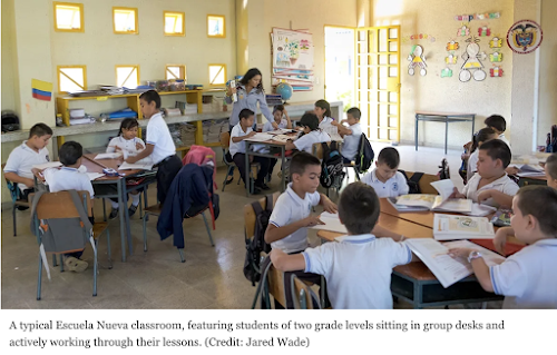A typical Escuela Nueva classroom, featuring students of two grade levels sitting in group desks and actively working through their lessons. (Credit: Jared Wade)