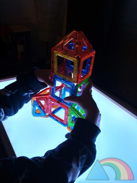 Cohete hecho con juego de construcción Magformers sobre mesa de luz