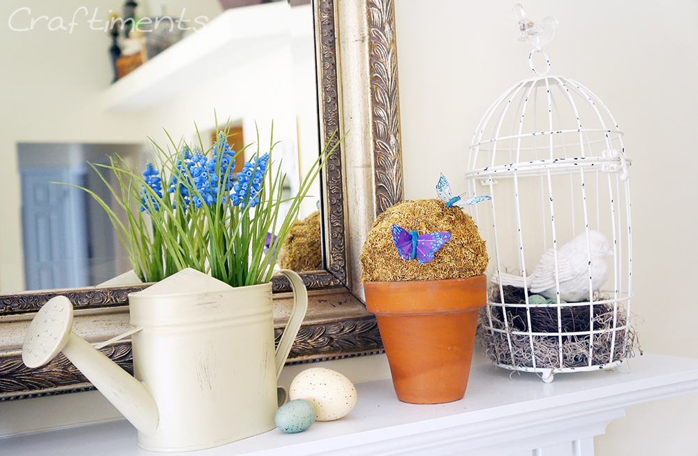 watering can with faux muscari, moss topiary, bird with nest in side birdcage