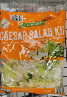 A terrible picture of a Little Salad Bar Caesar Salad Kit awkwardly posing inside an Aldi shopping cart