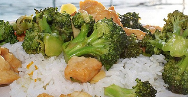 this is stir fried Asian food on a bed of rice it has chicken and broccoli along with pineapple