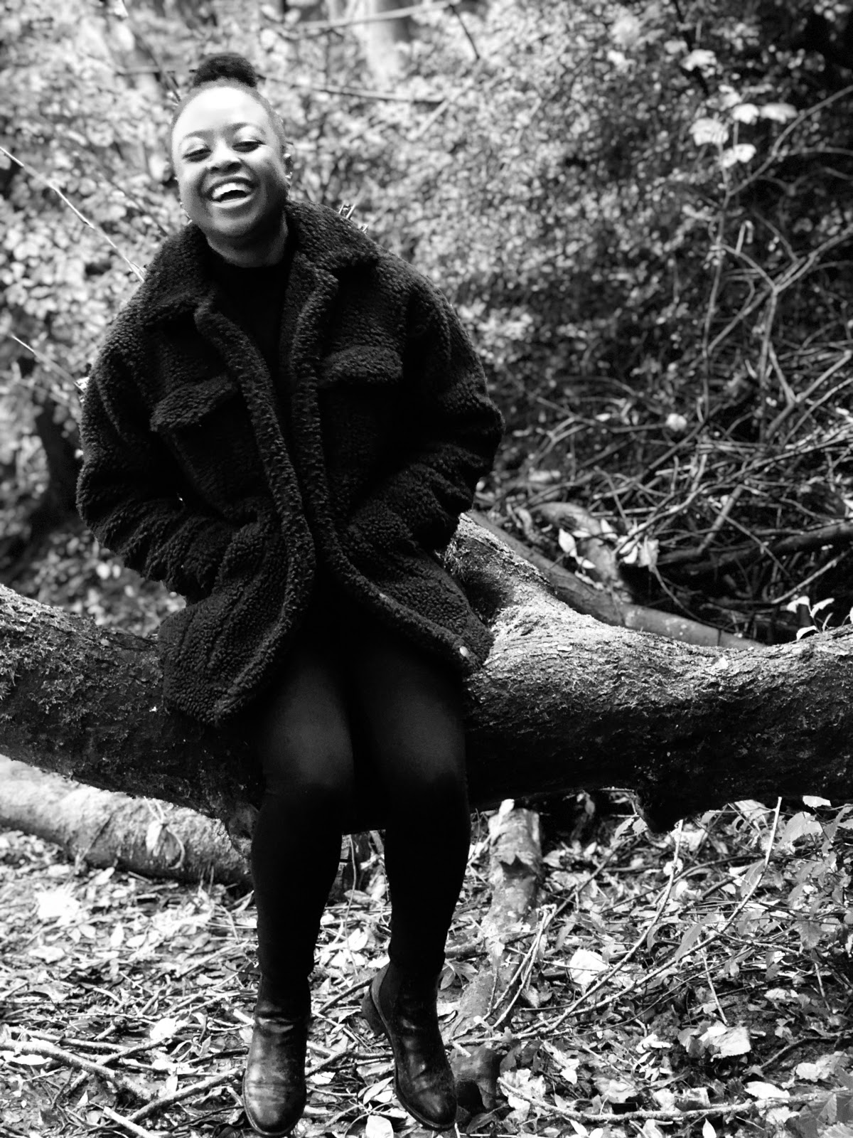 A candid shot of me laughing while sat on a wet tree branch in the middle of a forest