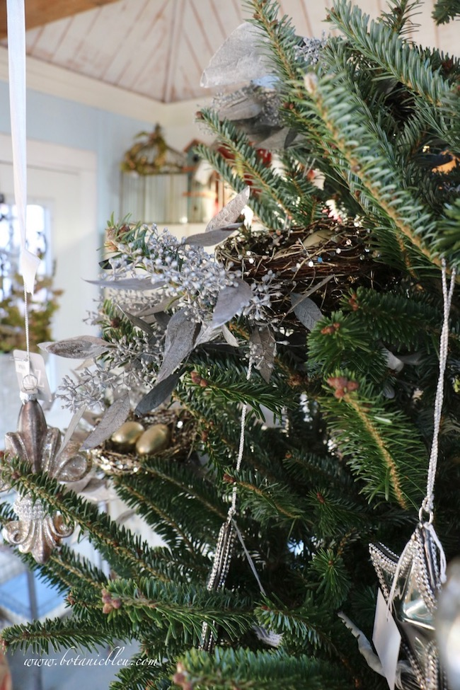 Silver colored preserved seeded eucalyptus sprigs lie underneath each bird's nest on the Christmas tree.