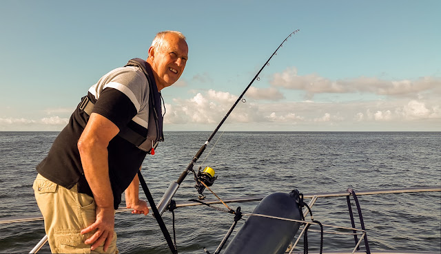 Photo of Phil setting up a fishing rod on Ravensdale's fore deck