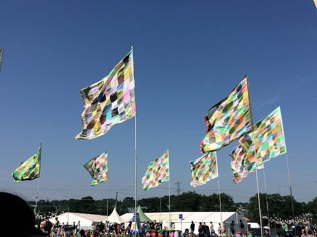 Flags waving in blue sky at Glastonbury Festival 2017