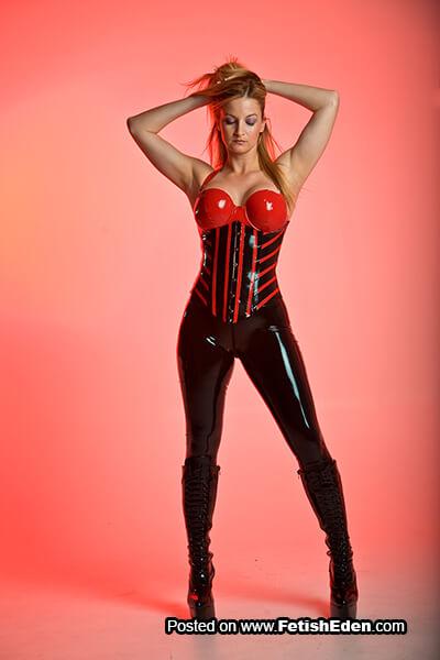 Red latex corset blonde in black latex leggings and long black PVC boots