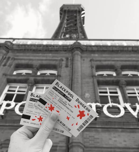 a black and white photo showing my hand holding up two Blackpool Tower Dungeon tickets in front of Blackpool Tower. I have edited red blood splatters on the tickets over the top.