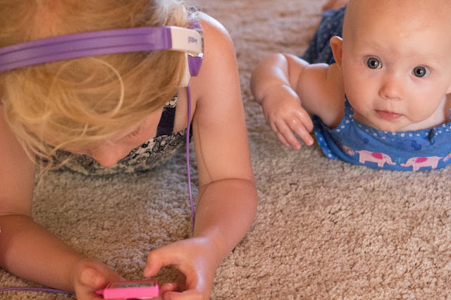 two children lying on a clean cream carpet one on an ipad the other dribbling which may void a warranty