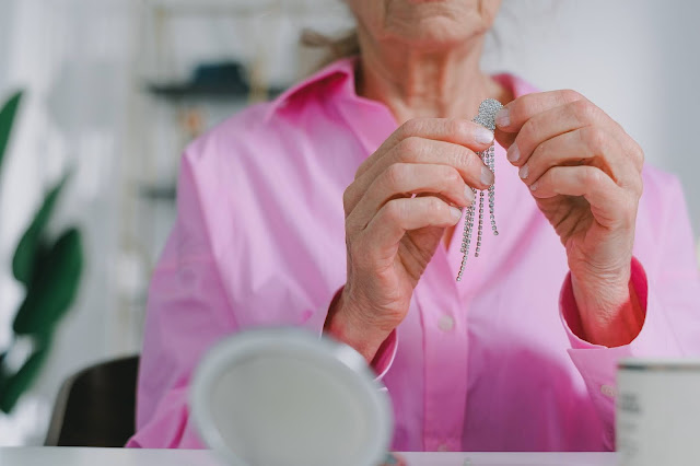 Person in a pink top putting on earrings.