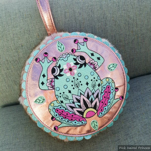 front of round handbag in pink fur and metallic with large embroidered frog