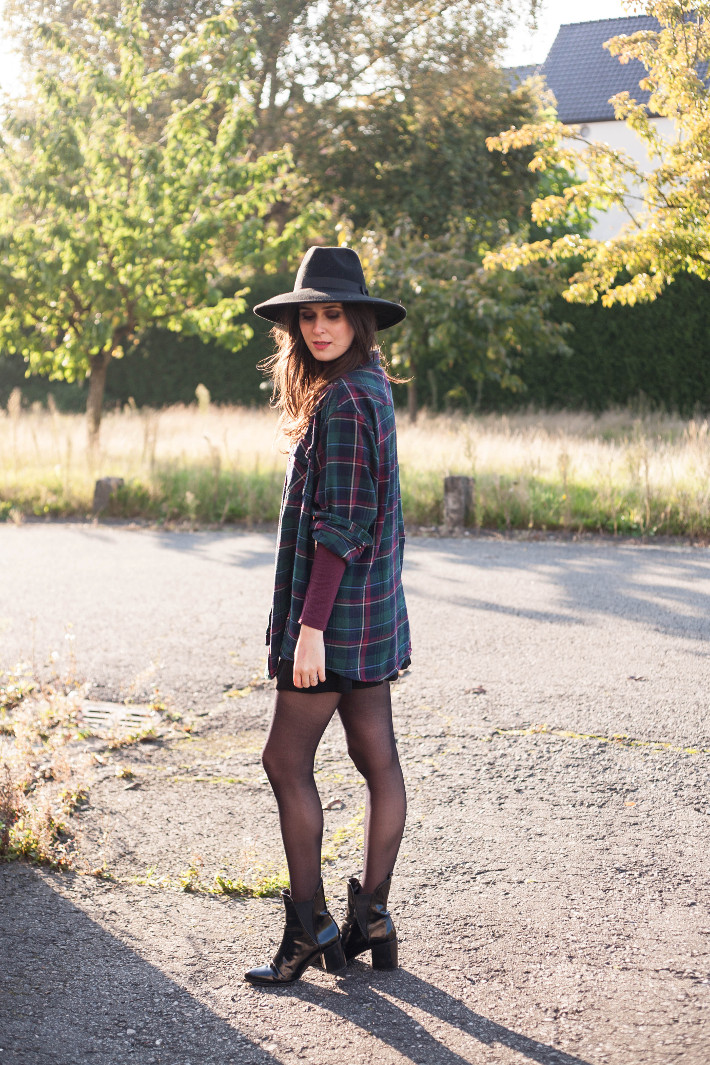 outfit: wide brim hat, plaid shirt layered over turtleneck, patent chelsea boots