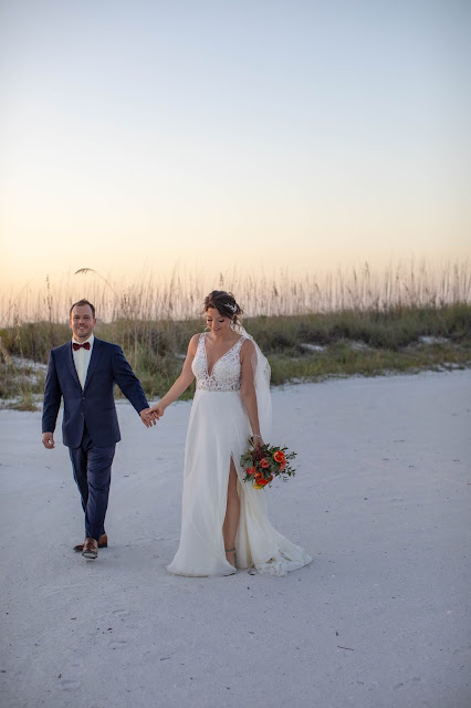 Newlywed couple walking in the sand with scenic beach view.