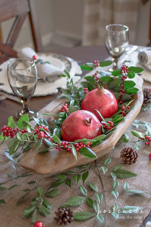 Christmas table centerpiece with wooden dough bowl with pomegranites and holly clippings