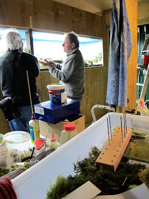 Two men in a workshop area, in front of a diorama in progress.