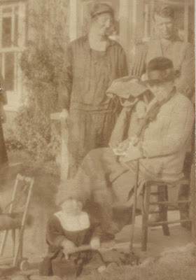 Family group, May and Fred House standing behind the siting Rebecca with baby Osborne sitting on the lawn
