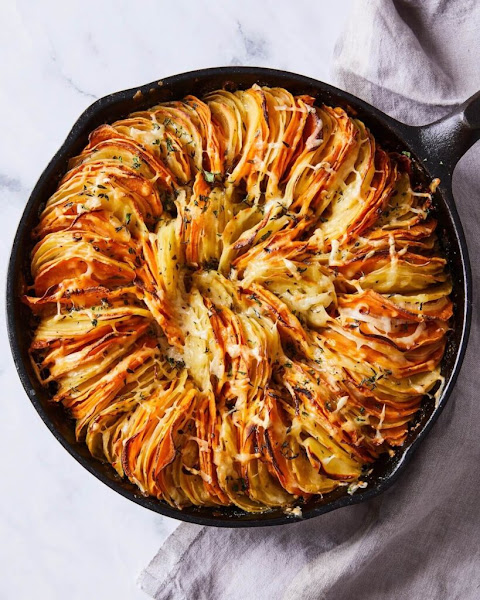 Top view of cheese and heb potato gratin in a cast iron skillet.