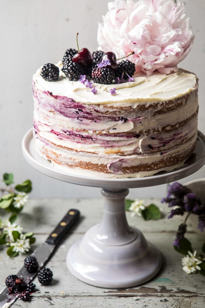 Blackberry Lavender Naked Cake with White Chocolate Buttercream - Four layers of light and fluffy vanilla cake with homemade blackberry lavender jam, and white chocolate buttercream. This cake is nothing short of delicious. Every bite is layered with fresh berries, hints of lavender, and sweet vanilla cake. The perfect berry filled cake for any and all occasions.