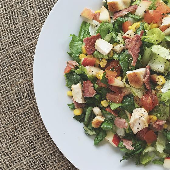 a chopped salad with chicken, turkey bacon and veggies