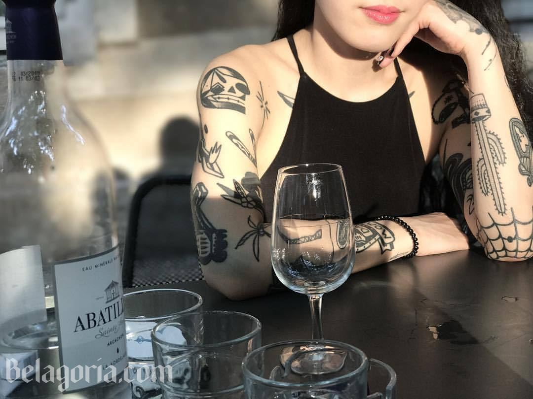 Una chica en un bar ccon tatuajes sencillos en los brazos