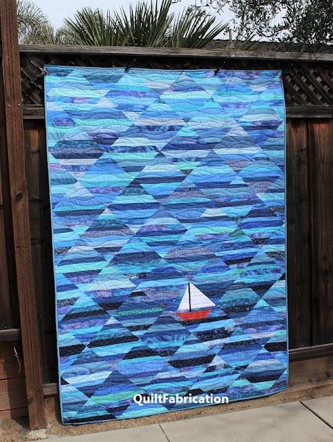 blue aqua ocean strip quilt with a red sailboat