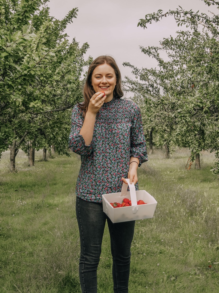 Brown haired girl in a floral blouse eating a strawberry and smiling