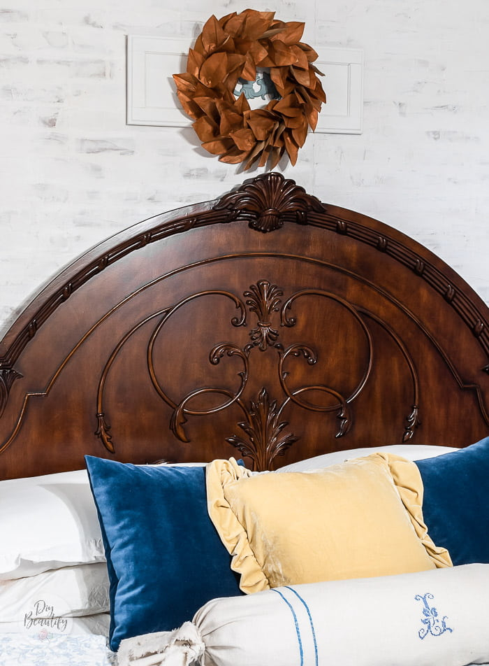 magnolia wreath hung above headboard, blue and yellow velvet pillows and French grainsack bolster pillow