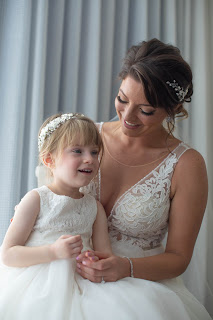 Bride and flower girl sharing candid moments.