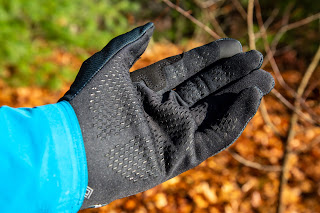 Close up view of the front of the black Stretch Mid Gloves worn on the hand, shown against a blurred background of orange leaves on the ground.