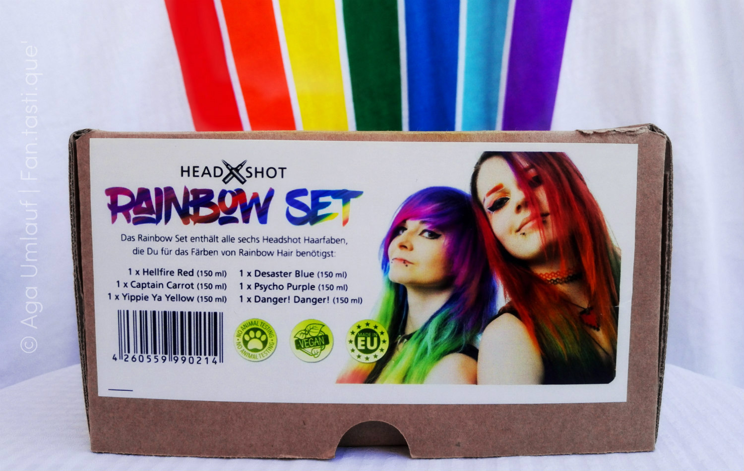 the packaging of the Headshot Rainbow Set in front of a vertical rainbow painting